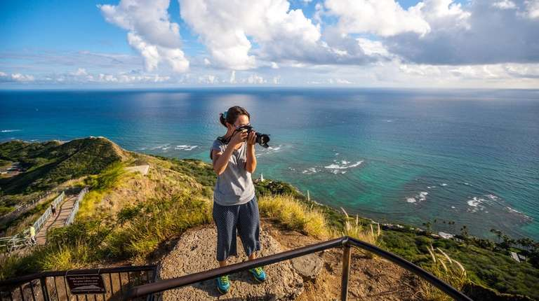 A woman photographs the view of Honolulu from