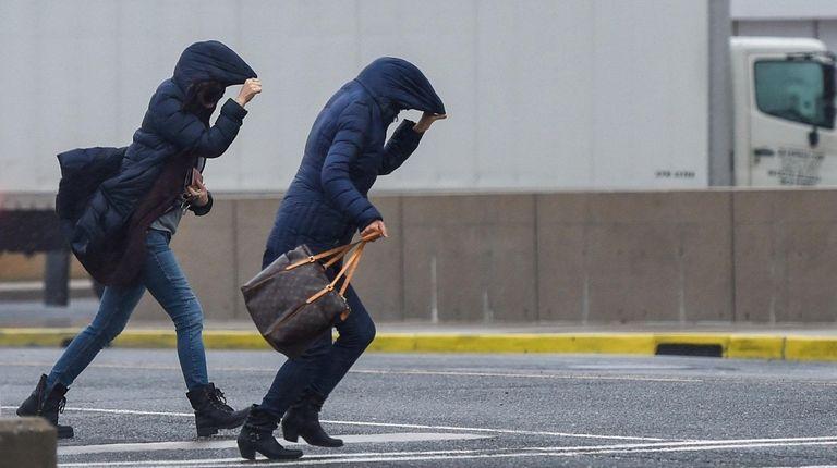 Pedestrians battle rain and wind in Central Islip