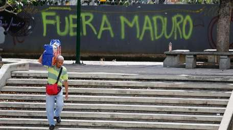 A man walks past graffiti on the wall