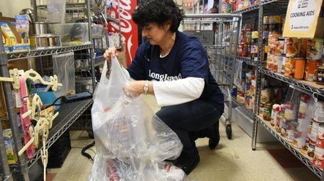 Volunteer Marilu Basile of Setauket weighs donations for