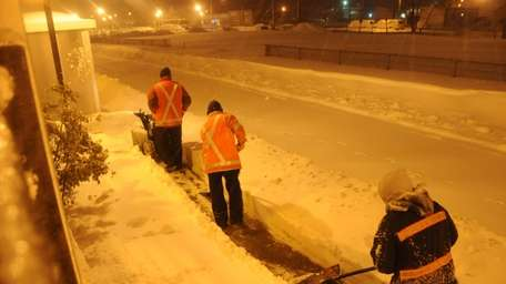 Workers clear snow outside the Ronkonkoma train station