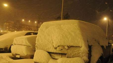 Cars blanketed with snow at the Ronkonkoma LIRR