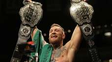 Conor McGregor holds up his title belts after