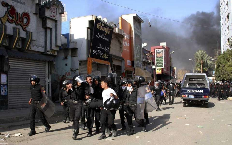 Egyptian police officers carry a wounded colleague in