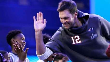 New England Patriots quarterback Tom Brady high-fives a