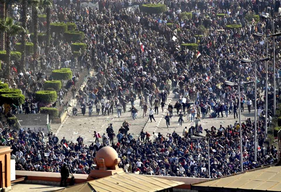 Pro-government demonstrators, bottom, clash with anti-government demonstrators, top,