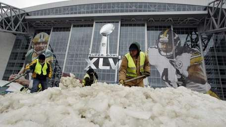 Workers clear ice outside of Cowboys Stadium earlier