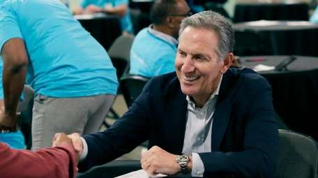 Starbucks CEO Howard Schultz, right, shakes hands with