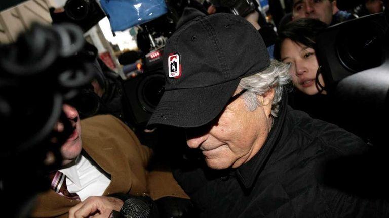 Bernard Madoff enters his house through a crowd