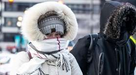 A bundled-up commuter makes her way through The