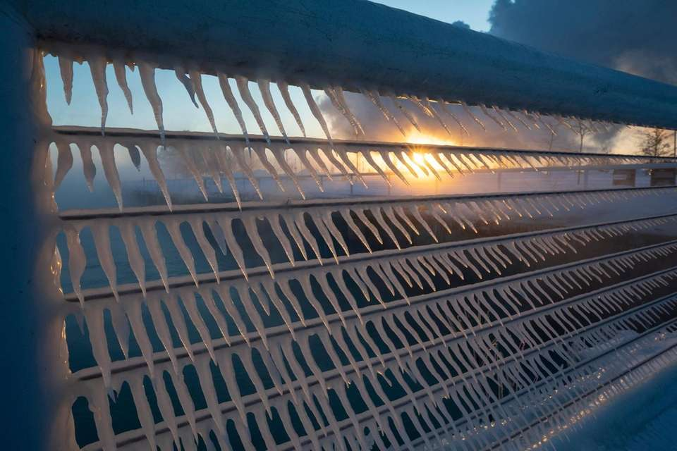 Icicles form on a railing at sunrise in