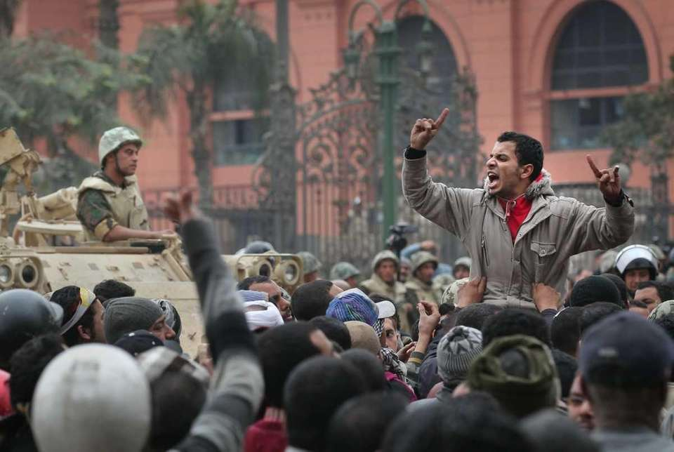 An anti-government protester chants and gestures in front