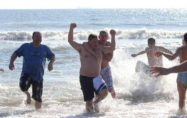 Revelers run out of the Atlantic Ocean during