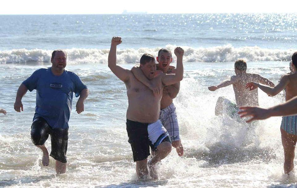 Revelers run out of the Atlantic Ocean during