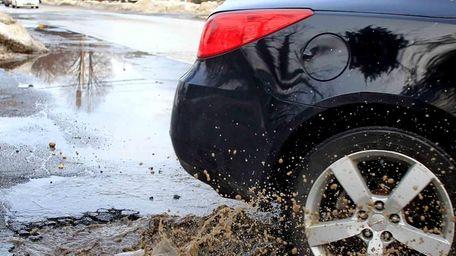 A car hits a pothole as it makes