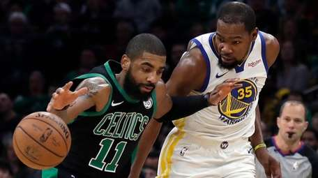 Celtics guard Kyrie Irving  dribbles against Warriors