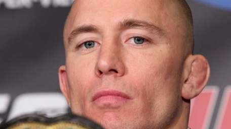 Georges St-Pierre peers over his championship belt at