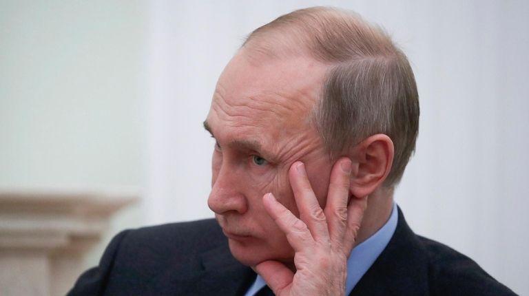 Russian President Vladimir Putin listens to Moldovan President