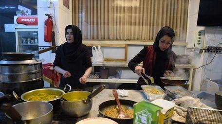 Afghan chefs work in a restaurant kitchen in