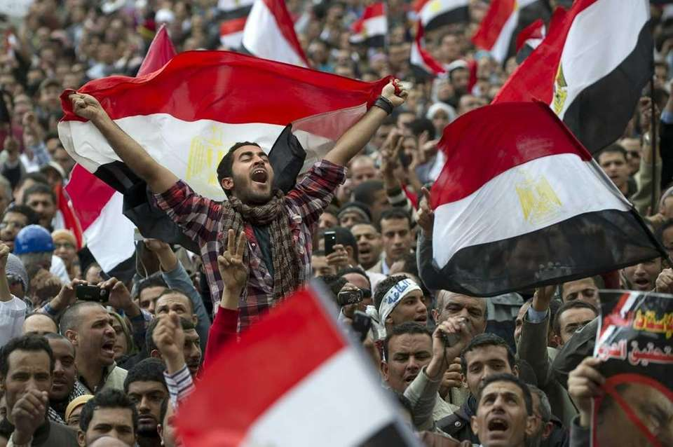Egyptian anti-goverment demonstrators wave Egyptian flags at Cairo's