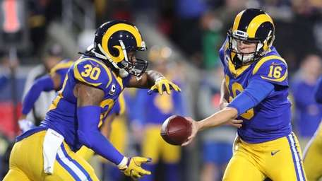 Rams quarterback Jared Goff hands off to running