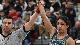 Adam Quintanilla of Lindenhurst, right, raises his arm