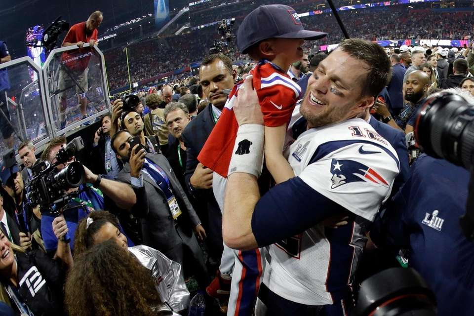 New England Patriots' Tom Brady lifts his son,