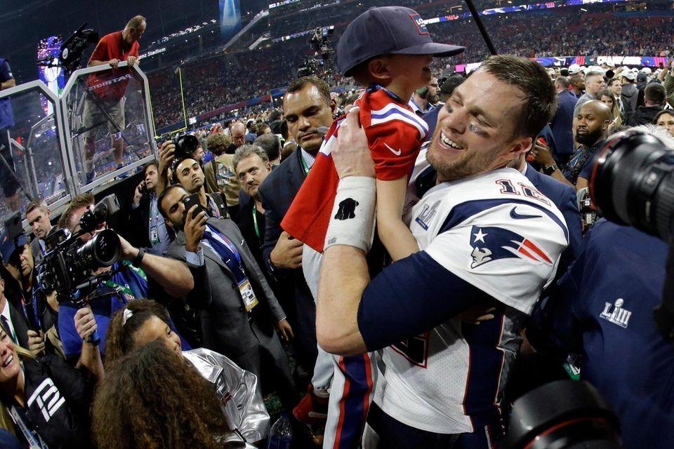 New England Patriots' Tom Brady lifts his son,