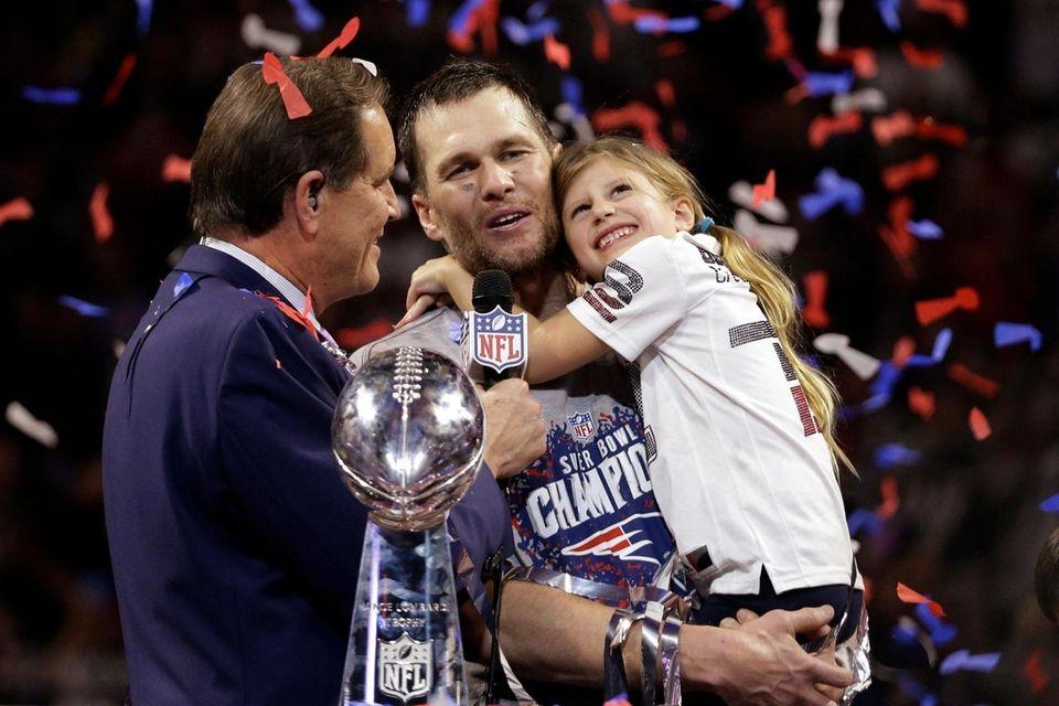 The Patriots' Tom Brady holds his daughter, Vivian,