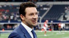 CBS football analyst Tony Romo walks across the
