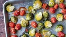 Brussels sprouts and grape cherry tomatoes are tossed