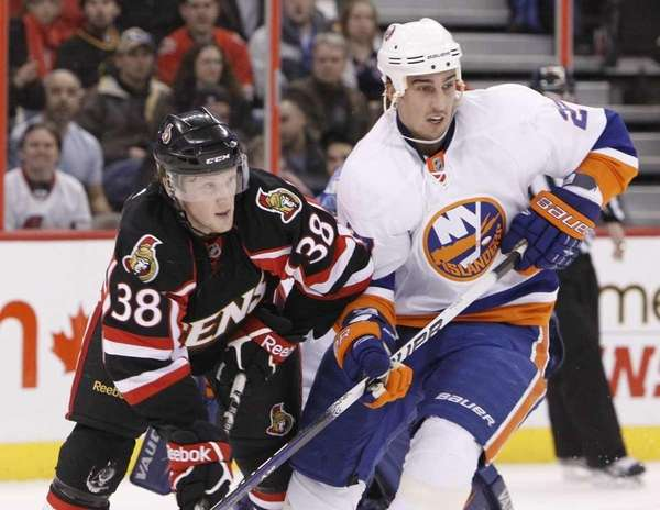 The Islanders' Milan Jurcina, right, battles against Erik