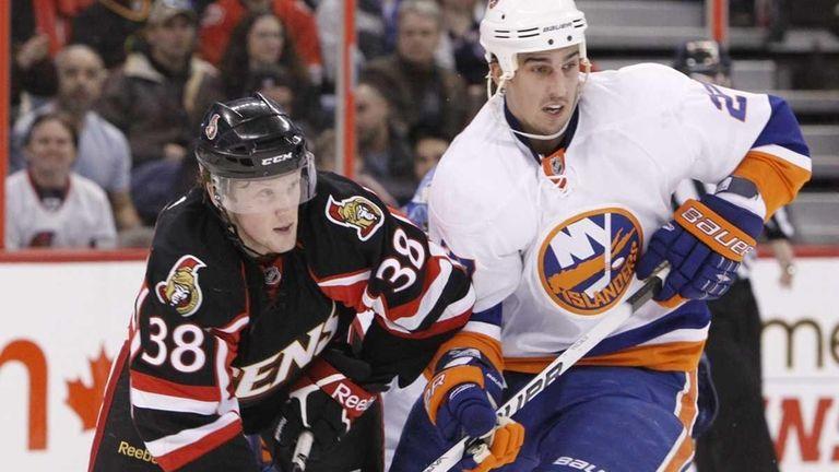 The Islanders' Milan Jurcina, right, battles against Erik