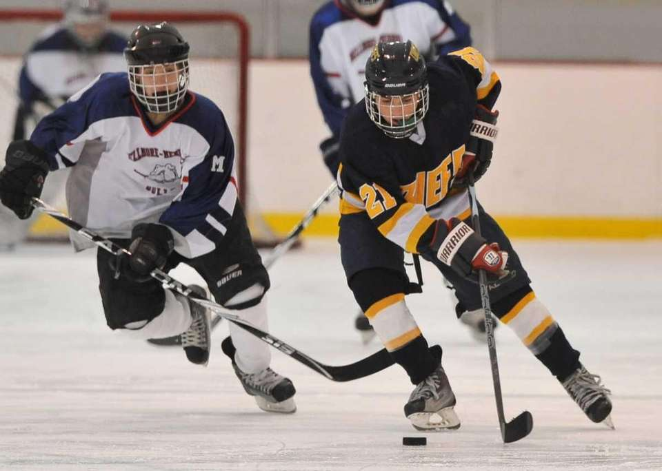 Massapequa's Nick Mangone, right, carries the puck up