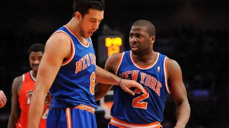 The Knicks' Landry Fields, left, holds off Raymond