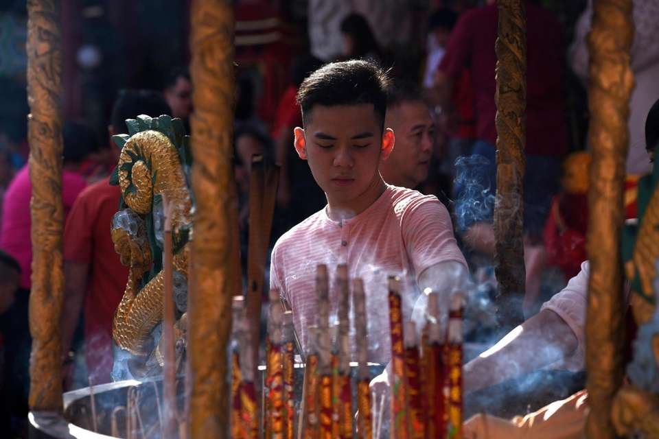 A participant burns joss sticks as he prays