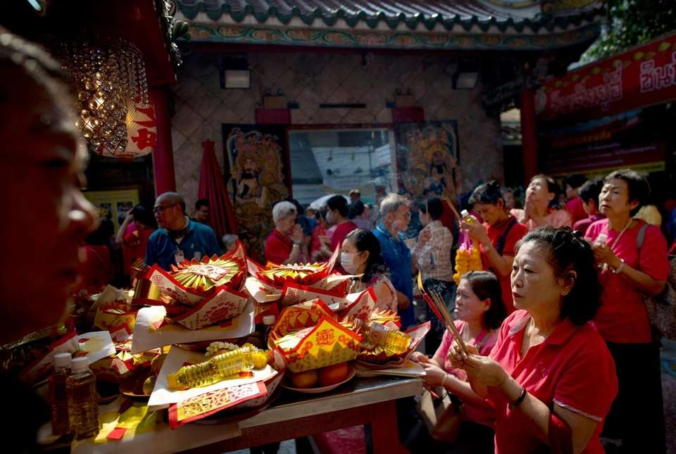 Ethnic Chinese Thai devotees burn incense sticks and
