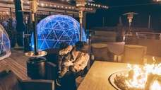 Families can relax inside outdoor heated igloos this