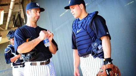 Catcher Russell Martin, right, speaks with Jorge Posada,
