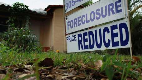 A foreclosure sign is seen in front of