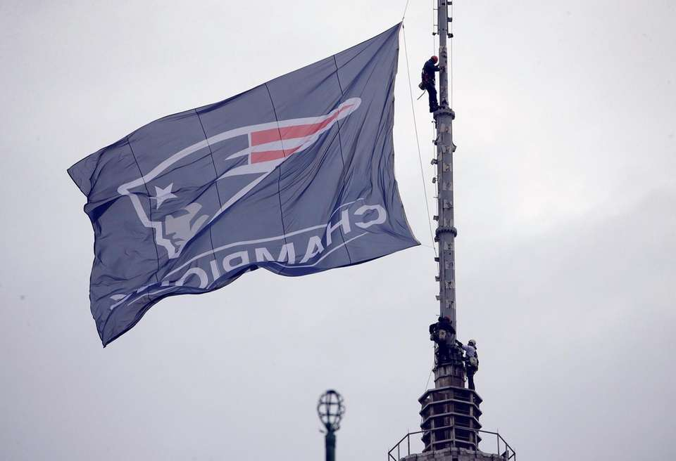 Workers secure a New England Patriots banner on