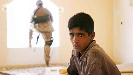 A young Iraqi worker pauses at a reconstruction