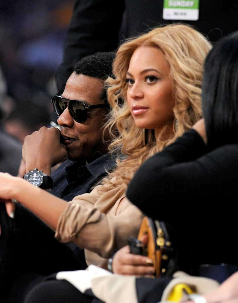 Rapper Jay Z and singer Beyonce Knowles sit
