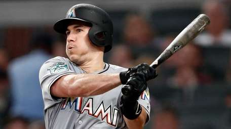 Marlins catcher J.T. Realmuto follows through on two-run