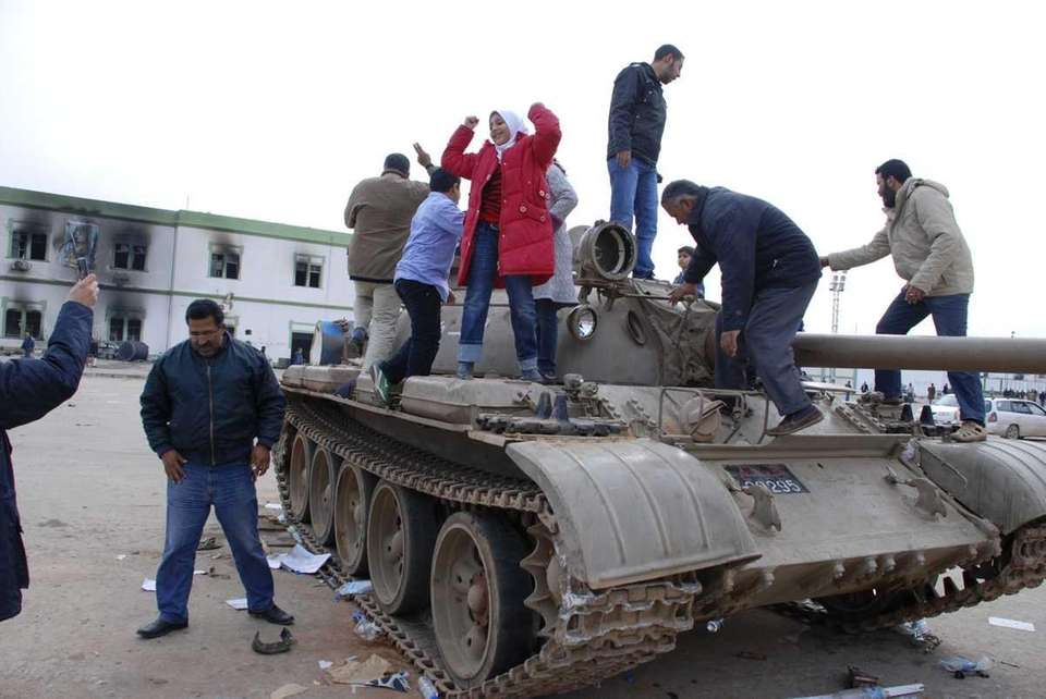Residents stand on a tank inside a security