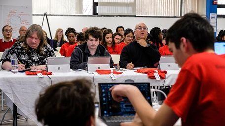 The judges listen as team members present their