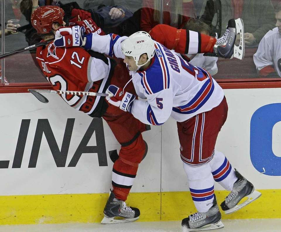 Carolina Hurricanes' Eric Staal is checked against the