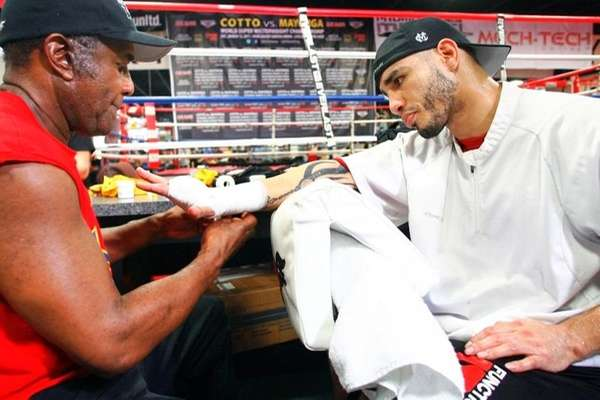 Miguel Cotto (L) listens to Emanuel Steward at