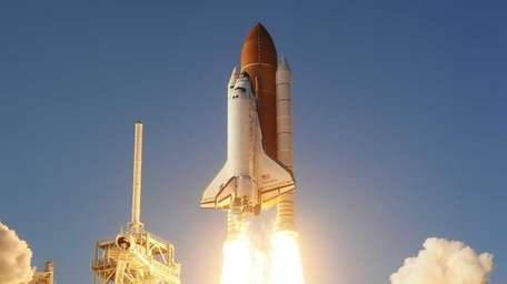 The space shuttle Discovery lifts off from Kennedy