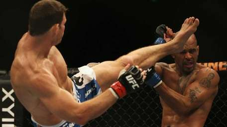 Michael Bisping, left, lands a kick to the